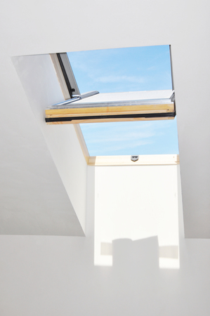 Opened attic skylight window with blue sky and fresh air. Stock Photo