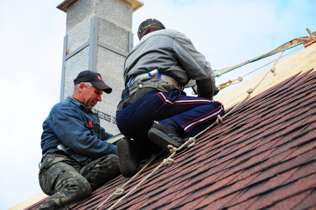 KYIV - UKRAINE SEPTEMBER - 15  2017: Roofers install asphalt shingles. Contractors laying asphalt shingles and repair roof after hurricane damage.