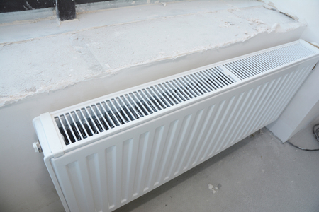 Installing metal white radiator heating with thermostat in new house construction. Foto de archivo
