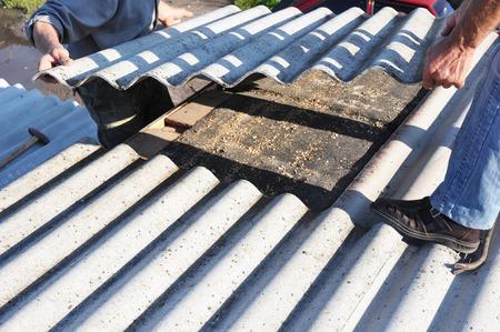 Asbestos workers repair asbestos roof. Asbestos removal.