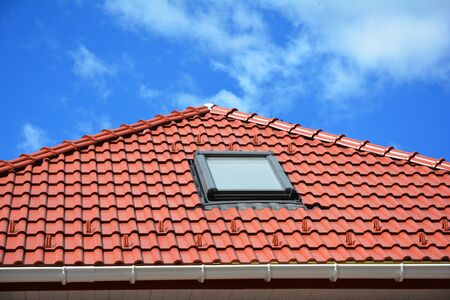 Attic skylights on the red clay tiled roof and snow protection against blue clouds sky.