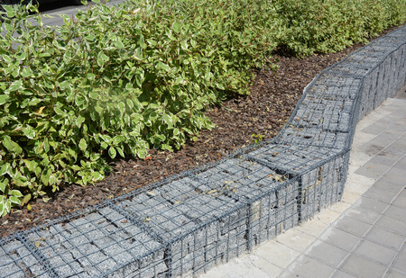 Modern Gabion fence with stones in wire mesh. Gabion wire mesh fencing with natural stones and bushes.