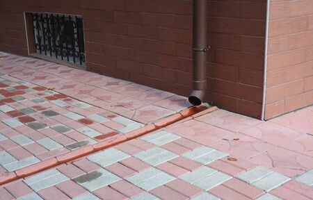 Roof gutter downspout pipe with drain in pavement. Rain gutter pipeline drainage. Stock Photo