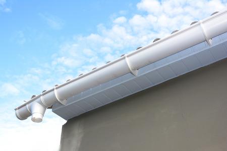 Réparation de gouttière. Installation de gouttière avec supports, drain de tuyau de descente. Maison inachevée Gouttière.