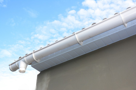 Roof gutter repair. Rain gutter installation with holders, drain downspout pipe. Unfinished house Guttering. Stock Photo