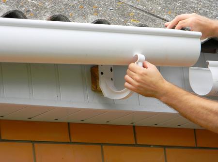 Contractor installing plastic roof gutter. Plastic Guttering, Rain Guttering & Drainage by Handyman hands.  Archivio Fotografico