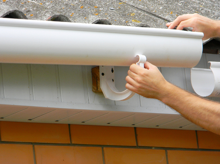 Contractor installing plastic roof gutter. Plastic Guttering, Rain Guttering & Drainage by Handyman hands.  Stock Photo