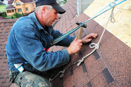 KYIV, UKRAINE - October, 24, 2017: Roofer laying asphalt shingles. Roofer with safety kit on the house roof installing, repair asphalt shingles.Roofing construction. Roofers Kits for Fall Protection.