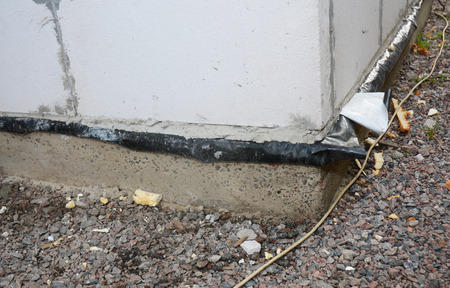 Waterproofing a brick house foundation membrane. Construction techniques for waterproofing basements and foundations. Reklamní fotografie