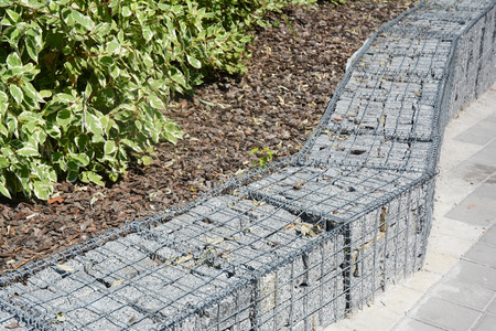 Modern Gabion fence with stones in wire mesh. Gabion wire mesh fencing with natural stones. Landscape design.