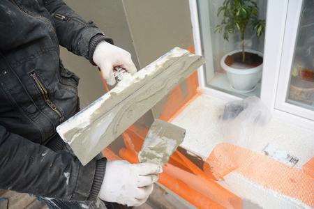 Man Hands Plastering, Stucco Wall Foam Board Insulation. Stock Photo