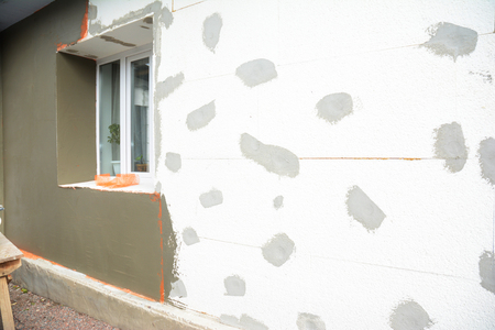 Unfinished house plastering wall with mesh, plaster mesh, rigid foam insulation. Window sill area insulation with stucco wall. Stock Photo