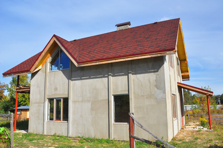 Installing House Roof with Asphalt Shingles and Plastering walls. Stucco walls after house insulation. Roofing Construction. Asphalt Shingles Roof Repair. Stock Photo