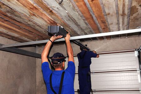 Contractors installing garage door opener. Repair garage door opener system.