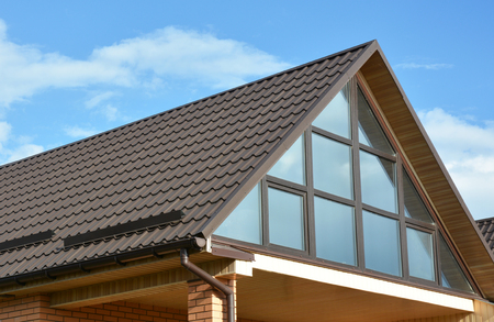 Metal roof with attic modern skylight window and rain gutter with roof waterproofing.