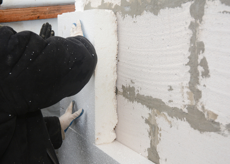 Builder installing rigid  insulation board for energy saving. Rigid extruded polystyrene insulation.