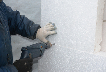 Builder drilling wall for installing anchors to hold rigid insulation foam board. How to attach rigid foam insulation to a concrete wall