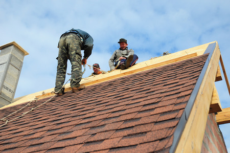 KYIV, UKRAINE - November, 22, 2017: Roofer laying asphalt shingles. Roofer with safety kit on the house roof installing, repair asphalt shingles.Roofing construction. Roofer's Kits for Fall Protection Editorial