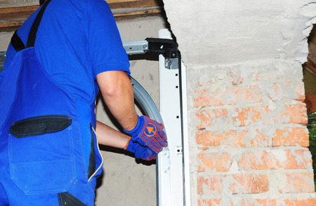 Close Up On Installing Garage Door Boards In New Brick House Stock