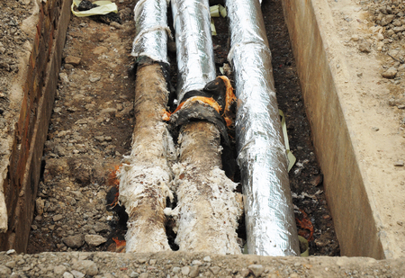 Repair, insulation and replacement of city sewer on the street. Pipes for water in an earthen trench. Stock Photo