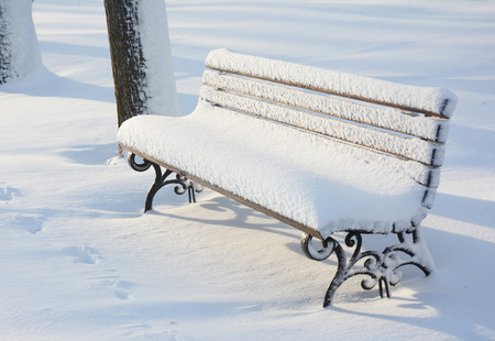 Park wooden bench after snowstorm. East Coast is frozen over in a bomb cyclone.
