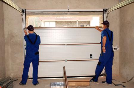 Entrepreneurs installant, réparant, isolant une porte de garage. Joint de porte de garage, remplacement de porte de garage, réparation de porte de garage.