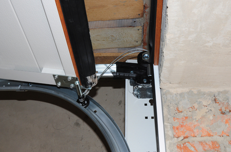 Contractor  repair and install garage door. Replace a Broken Garage Door Spring. Garage Door Spring Repair and Replacement. Фото со стока