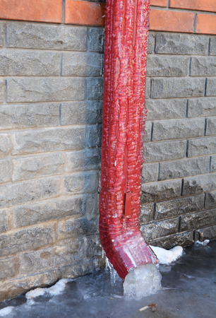 Frozen Gutter or Downspout. Gutters and Downspouts Sometimes Freeze into Solid Blocks of Ice. Bad rain gutter cleaning.