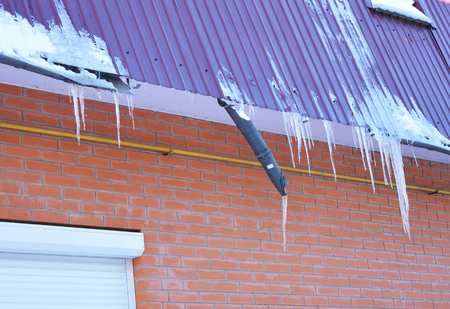 Broken Rain Gutters. Ice dam. Closeup on new broken rain gutter system without roof protection Snow guard on house construction. Icicles damage roof and gutter. Ice Damming. Ice dams.