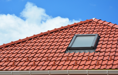 Attic window skylights on the red clay tiled roof. Stock Photo