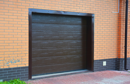 Garage Door Installation, Repair with ventilation system, rain gutter and pavement. Stock Photo
