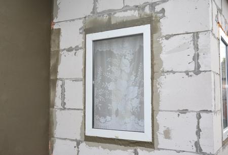 Unfinished house plastering wall with fiberglass mesh, plaster mesh, rigid foam insulation, stucco, window insulation.  Stock Photo