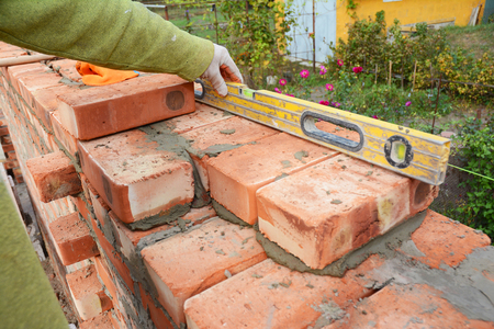 Bricklayer Using a Spirit Level to Check New Red Brick Wall Outdoor. Bricklaying Basics Masonry Techniques. Stockfoto