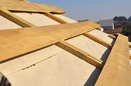 Roof Waterproofing Membrane Coverings. Wooden Construction Home Framing with Roof Rafters.  Stock Photo