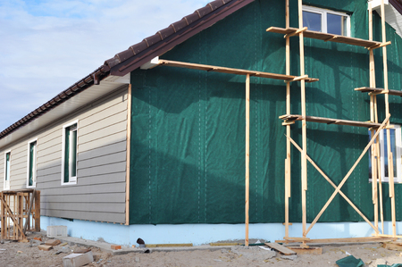 Building house with wall insulation, waterpfoof membrane, plastic siding, guttering and foundation insulation with styrofoam. Siding House, Siding installation.