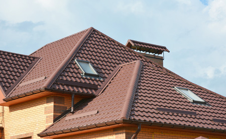Metal roof with modern house attic construction with roof guttering and attic skylight window.  Attic skylights. Roofing construction problem area. Stock Photo