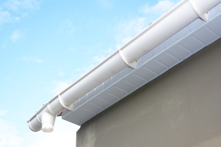 Roof gutter repair. Rain gutter installation with drain downspout pipe. Guttering with soffits and fascia board.