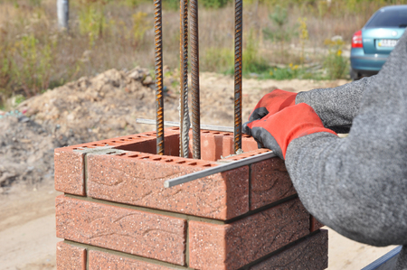 Closeup on brick laying blocks correctly on fence brick column. Whether you are laying brick to build a mailbox enclosure, or building a brick house, the process is the same.
