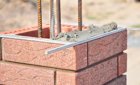 Bricklaing brick pillar with iron bars.