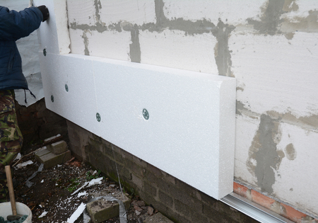 Building contractor insulating House Wall with styrofoam insulation sheets.