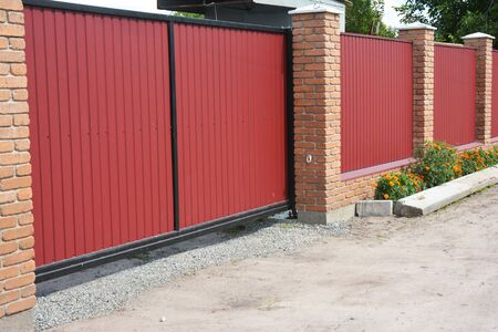 Installing house red metal fence with garage gate of modern style design and flower bed.