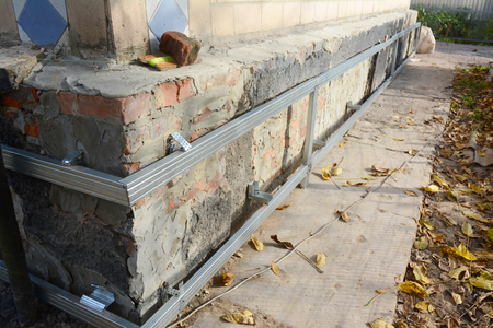 House foundation wall repair,  renovation  with installing metal sheets on metal frame for waterproofing and protect from wetness.  Stock Photo