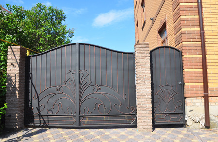 Forged gate and house metal door. Metal Gates - Gates & Metal Railings. Banque d'images