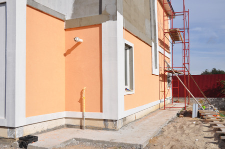 Close uop on unfinished house paining walls and concrete path for foundation waterproofing.