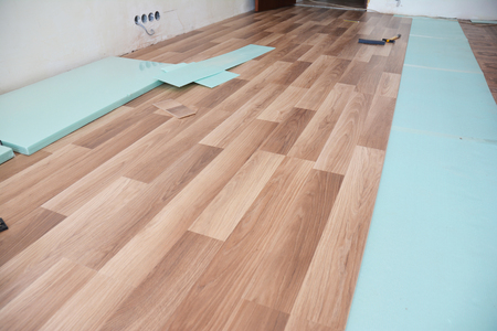 Installing wooden laminate flooring with insulation and soundproofing sheets.