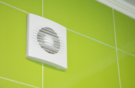 Bath vent fan with green tiles wall. White bathroom ventilation system.