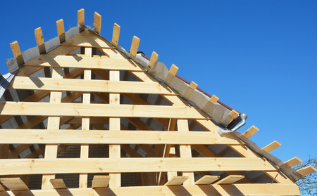 House attic wooden roofing construction. Installing wooden rafters, logs, eaves, timber.