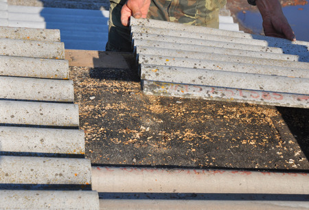 Old and danger asbestos removal. Roofers replace damaged asbestos tile. Repair asbestos roof.