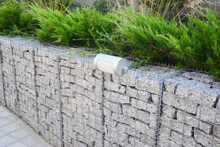 Gabion fence with stones in wire mesh and outdoor lighting. Gabion wire mesh fencing with natural stones and savin juniper.
