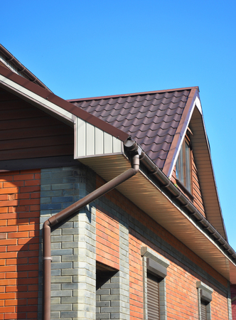 Attic metal roof with brown plastic roof gutter and soffit boards. Stock Photo